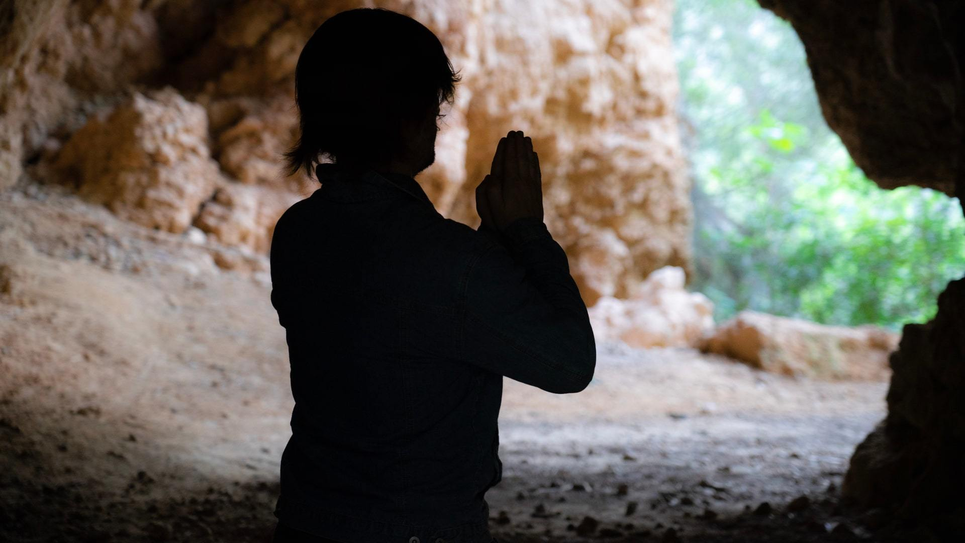 Man praying in cave Mallorca min