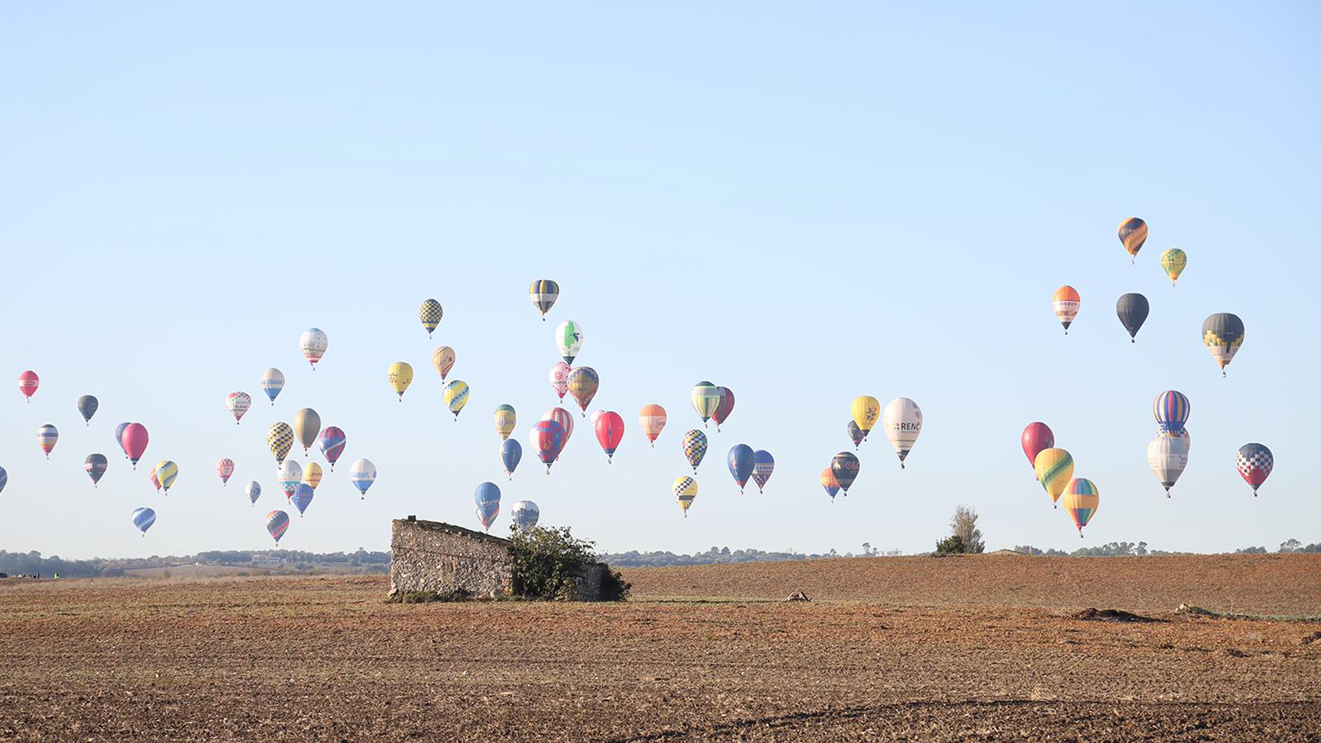 A hundred hot air balloons over Mallorca fields countryside
