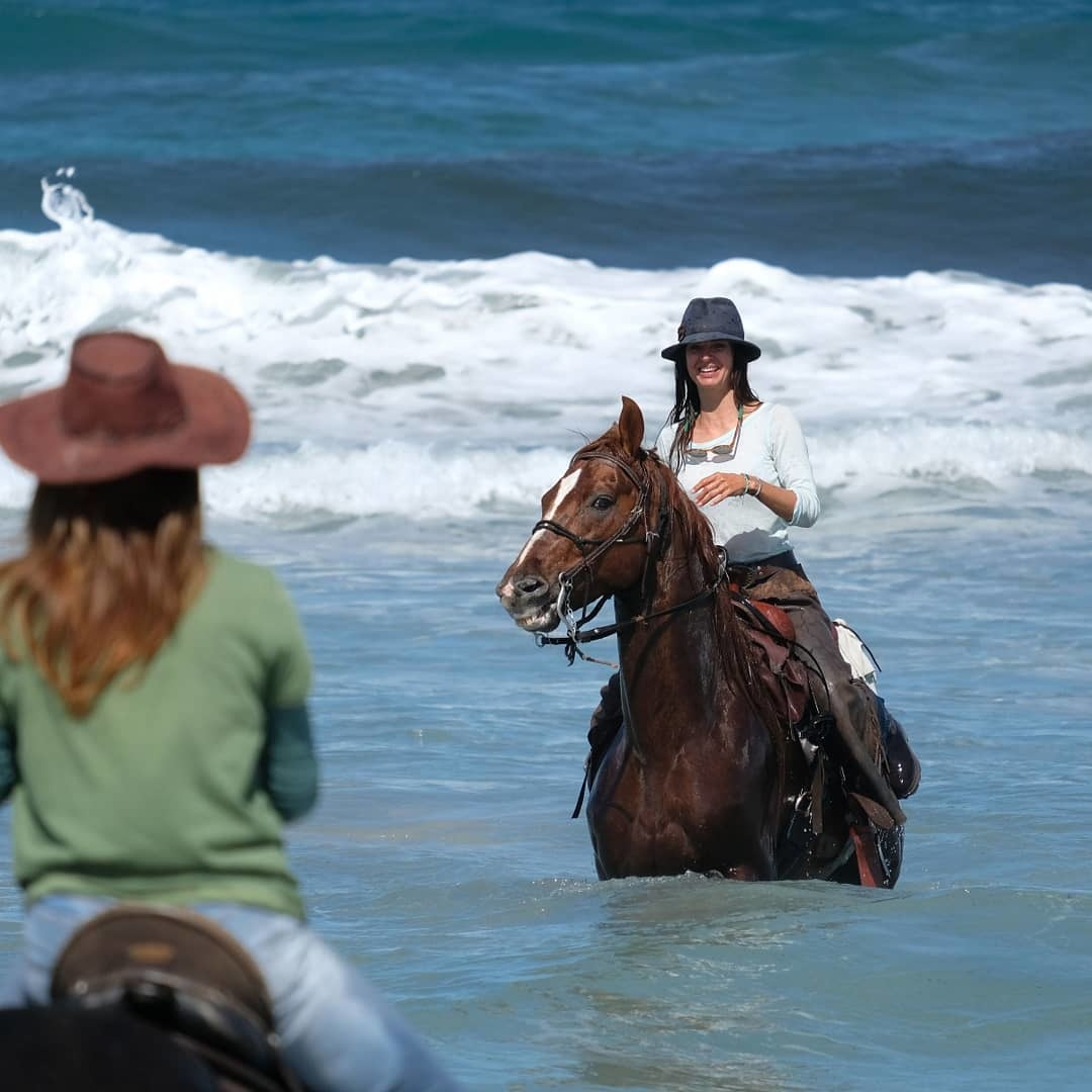 Girls on beach on horseback